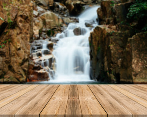 Wooden board empty table in front of blurred background. Perspective brown wood over blur waterfall in forest - can be used for display or montage your products. spring season. vintage filtered image.