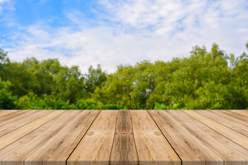 Aluminium Prints Garden Wooden board empty table in front of blurred background. Perspective brown wood over blur trees in forest - can be used for display or montage your products. spring season. vintage filtered image.