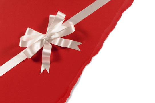 Gift ribbon and bow in white satin on untidy torn red paper back