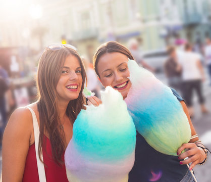 young women holding cotton candy and enjoying outdoor