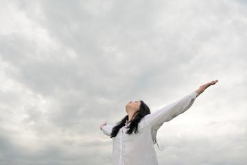 Junge Frau jubelt, Wolkenhimmel