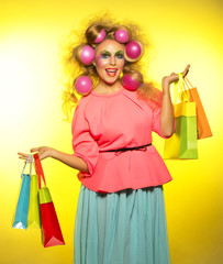 Girl with bright makeup with balloons in hair and purchase in hands