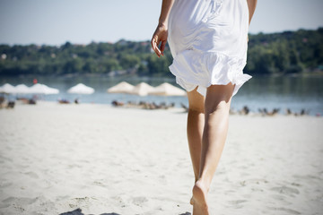 Woman in white running on beach