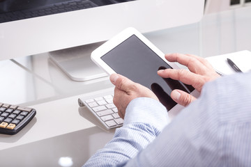 Anonymous business man typing on mobile device on office desk, v