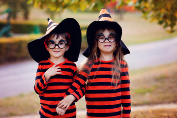 Boy and girl in the park in halloween costumes, having fun Wall mural
