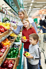 Mother and children with bell pepper in supermarket