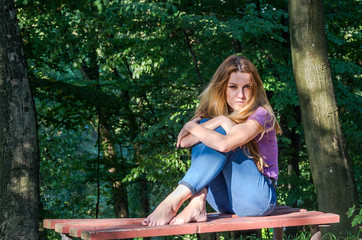 Young beautiful girl model in jeans and a T-shirt with long blond hair and sad smiles pensively posing for a walk in the autumn park sitting on a bench among the trees and vegetation