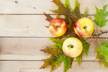 Red apples and autumn yellow maple leaves on a wooden table, close up, selective focus