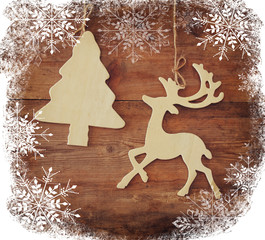 image of wooden decorative christmas tree and reindeer hanging on a rope over wooden background with snowflake overlay