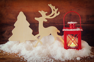 christmas background with red lantern, wooden decorative reindeer and tree on the snow over wooden background