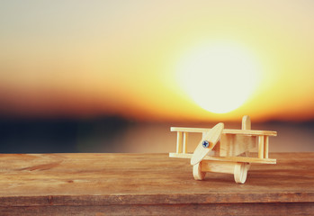 image of wooden toy airplane over wooden table against sunset sky. retro style image