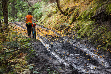 Bikers travel in difficult conditions in autumn forest