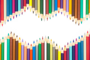 Wave shaped of multiple colour wooden pencil on white background