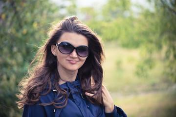 Woman in blue jacket in green summer park
