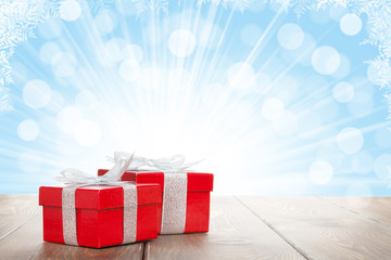 Christmas gift boxes on wooden table with bokeh