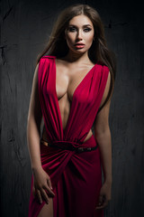 Fashion model in beautiful red dress in studio