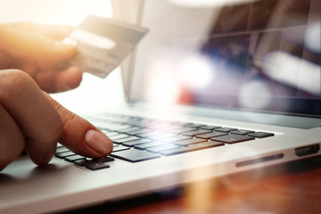 close up of hands using laptop and holding credit card  as Onlin