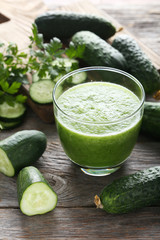Glass of fresh cucumber juice on grey wooden table