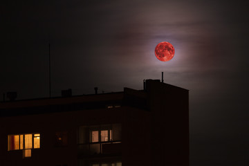 Red full moon in red color also called bloodmoon on the background of building.