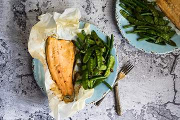 Baked fish with beans on rustic background