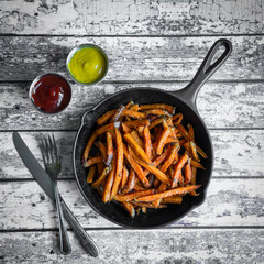Sweet potato fries in cast iron skillet on wooden background