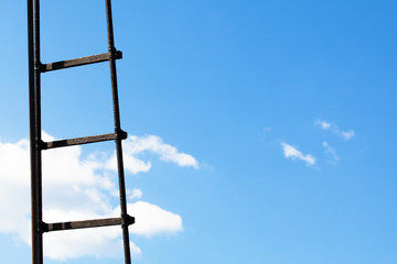 Ladder against a bright blue sky with clouds