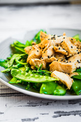 Grilled chicken with spinach,arugula and peas on rustic wooden b