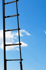Ladder against a bright blue sky with clouds. Vertical