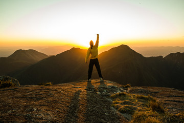 Man celebrating success on top of a mountain