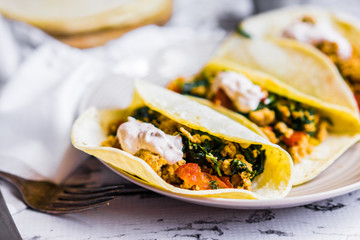 Tacos with chicken and vegetables on white wooden background