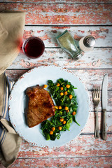 Fresh steak with green salad on rustic wooden background