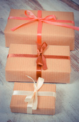 Vintage photo, Wrapped gifts for Christmas or other celebration on old wooden background