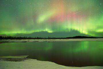 Aurora Borealis Northern Lights over lake in winter at Fairbanks Alaska