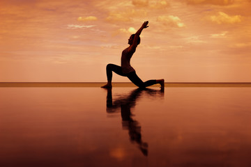 silhouette Reflextion of low lunge in Yoga pose with sunset background