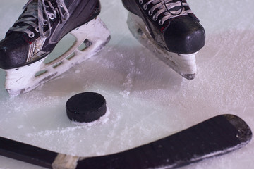 hockey sticsk and puck on ice