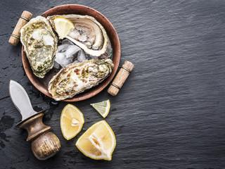 Fototapeten Schalentier Raw oysters on the graphite board.
