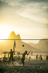 Silhouettes of Brazilians playing a beach ball game in the sand between volleyball nets against a backdrop of Dois Irmaos Mountain on Ipanema Beach, Rio de Janeiro Brazil