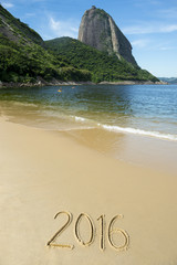 Simple 2016 message handwritten on smooth sand of Red Beach Praia Vermelha with a view of Sugarloaf Mountain in Rio de Janeiro Brazil