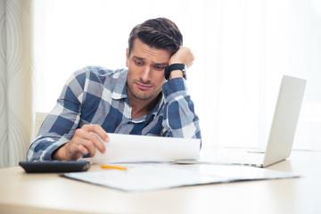 Portrait of a sad man looking at bills