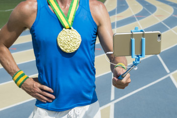 Gold medal athlete standing at running track taking a selfie on his mobile phone with selfie stick