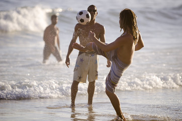 Pair of young carioca Brazilian men plays football on the shore of Ipanema Beach in a game known locally as altinho