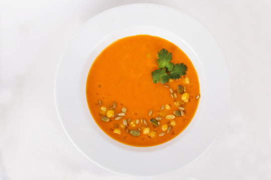 Pumpkin soup with seeds and parsley on top of the menu