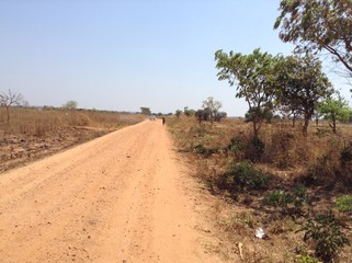 A car passes on a rural road as a boy carrying water also walks along in rural Lusaka; Zambia; Africa.