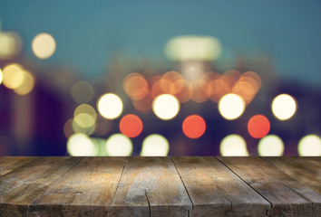image of wooden table in front of abstract blurred background of city lights