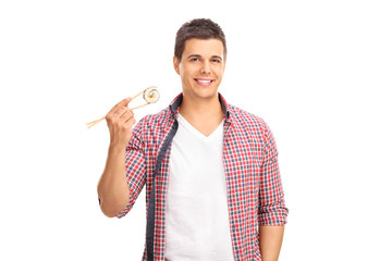 Man holding a piece of sushi on Chinese sticks