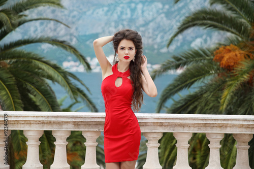 637af3a6cb Beautiful young brunette girl model in red dress standing on Bal ...