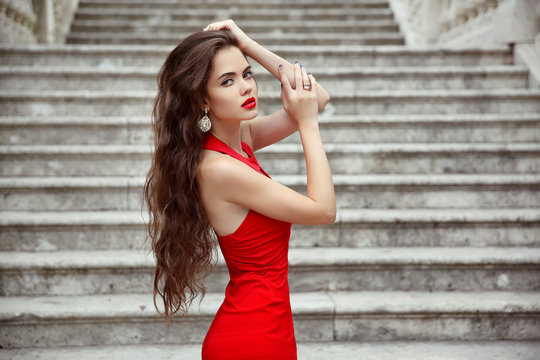 Beautiful brunette girl in red dress with long healthy hair posi