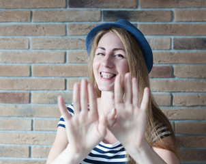 funny young woman with braces on his teeth on brick wall backgro