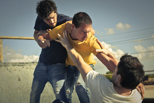 Three young guys in a fight