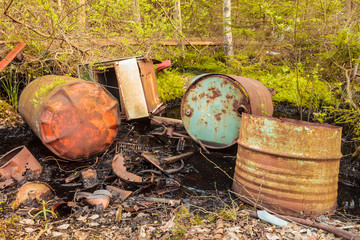 Rusted waste barrels in a forest